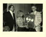Tom Collins, Barbara Mandrell, and Jim Foglesong with a gold record
